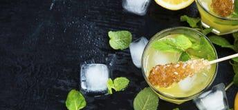 Cocktails de citron avec la menthe et les glaçons sur le fond foncé, Moji Photographie stock libre de droits