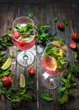 Cocktails de fraise avec la chaux et les glaçons sur le fond rustique photographie stock