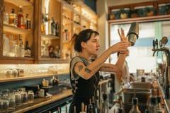 Cocktails de mélange de jeune barman féminin derrière un compteur de barre photographie stock libre de droits