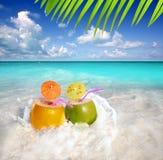 Cocktails de noix de coco dans l'éclaboussure tropicale de l'eau de plage Photos libres de droits