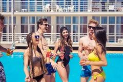 Cocktails et bière potables de personnes pendant la partie à la piscine Image stock