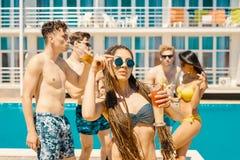 Cocktails et bière potables de personnes pendant la partie à la piscine Photographie stock libre de droits