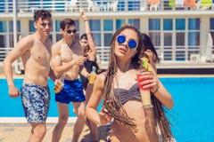 Cocktails et bière potables de personnes pendant la partie à la piscine Images stock
