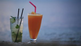 Cocktails at evening seashore. Close up shot of two fruity alcoholic cocktails mojito and orange juice standing side by side in their tall glasses in the sand on stock video