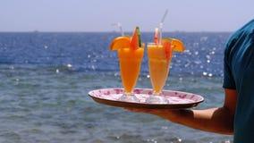 Cocktails exotiques dans un verre avec une paille sur un plateau sur le fond de la mer ?gypte clips vidéos