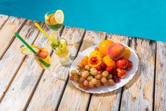 Cocktails and fruits by the pool. stock image