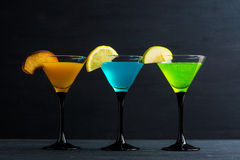 Cocktails garnished with fruits. On the black wooden background royalty free stock photography