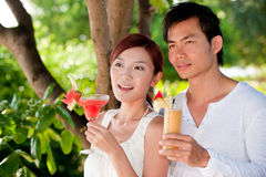 Cocktails on holiday. An attractive young couple relaxing on holiday with drinks royalty free stock images
