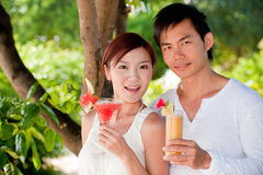 Cocktails on holiday. An attractive young couple relaxing on holiday with drinks stock image