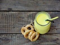 Cocktails jaunes de boisson au lait et un groupe de petits bagels sur un fond en bois Photos stock