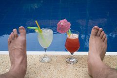 Cocktails and male`s feet at the edge of the outdoor pool. Closeup of cocktails and male`s feet at the edge of the outdoor swimming pool Royalty Free Stock Photography