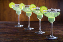 Cocktails of Margarita in row. Four glasses of classical Margarita cocktail with salty edge and lime slices stock photo