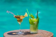 Cocktails at poolside. Two cocktails on wooden table next to swimming pool Stock Photo