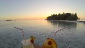 Cocktails potables avec une vue d'île au coucher du soleil banque de vidéos