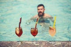Cocktails potables d'homme à la piscine luxueuse en hôtel, relaxation et tourisme image stock