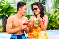 Cocktails potables de couples asiatiques à la piscine Photo stock