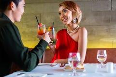 Cocktails potables de couples asiatiques dans la barre de fantaisie Photos stock