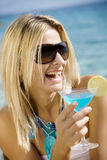 Cocktails by the sea. Laughing woman drinking cocktail by the sea Royalty Free Stock Image