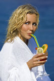 Cocktails By The Sea. A beautiful young blond woman in a white bath robe happily drinking a cocktail in front of a blue sea and bathed in summer sunshine Stock Photo