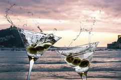Two cocktails with splashing martini and olives on a sunset beach stock photography