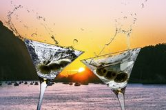Two cocktails with splashing martini and olives on a sunset beach stock photos