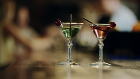 Cocktails standing on a bar counter. Close up view of two martini glasses with cocktails standing on a bar counter stock footage
