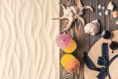 Cocktails and straw hat with seashells on light sand stock photo