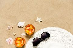 Cocktails, sun hat and sunglasses on beach sand stock photography