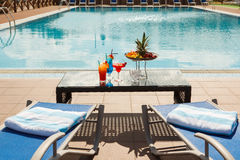 Cocktails. Sun lounges and cocktails by the pool Stock Photography