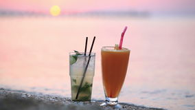 Cocktails at sunset. Close up shot of two fruity alcoholic cocktails mojito and orange juice standing side by side in their tall glasses in the sand on a stock footage