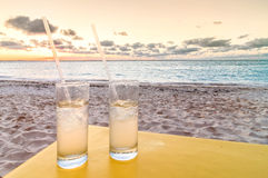 Cocktails on tropical beach at sunset stock photography