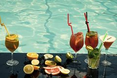 Cocktails at water pool. Drink, food and relax. Fruit slice and cocktail glass at bar. Alcoholic beverage and fruit at restaurant. Party and summer vacation Royalty Free Stock Photos