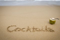 Cocktails written in sand with a coconut on the side. Royalty Free Stock Photography