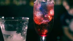 Cocktale vermelho com gelo na barra filme