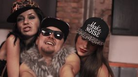 Cocky hip hop man in fur vest with women stsitting on bed rapping. Cocky caucasian hip hop man in fur vest with glasses and snapback with women in underwear stock footage