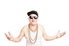 Cocky senior rapper gesturing with his hands. Cocky senior man in a hip-hop outfit gesturing with his hands and looking at the camera isolated on white Royalty Free Stock Images