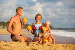 Cocnut питья семьи на пляже на заходе солнца Стоковое Изображение RF
