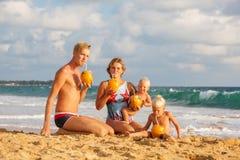 Cocnut питья семьи на пляже на заходе солнца Стоковое Изображение