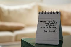 Coco Chanel cite écrit sur une note de bloc images stock