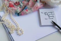 Coco Chanel cite écrit sur une note de bloc, des accessoires de perle et une chemise soyeuse de fleur images stock