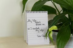 Coco Chanel quotes written on a block note and potted houseplant. Inspiration phrase `My life didn `t please me, so I created My Life stock photos