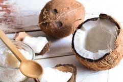 Coco con aceite de coco en tarro en fondo de madera Imagen de archivo libre de regalías