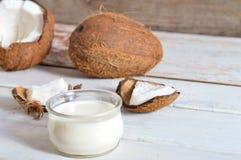 Coco con aceite de coco en tarro en fondo de madera Imagenes de archivo