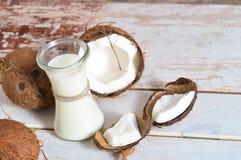 Coco con aceite de coco en tarro en fondo de madera Fotos de archivo