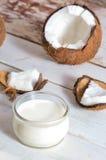 Coco con aceite de coco en tarro en fondo de madera Foto de archivo libre de regalías