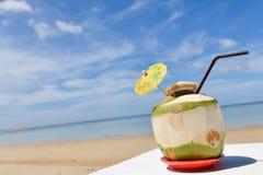 Coco con la paja de beber en el mar Foto de archivo