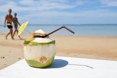 Coco con la paja de beber en el mar Fotos de archivo libres de regalías