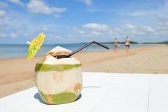 Coco con la paja de beber en el mar Imágenes de archivo libres de regalías