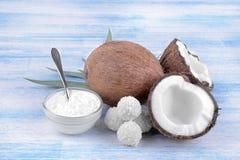 Coco con los dulces del coco y el aceite de coco en un fondo de madera azul Fotos de archivo