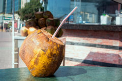 Coco con una paja a beber en la tabla refresco Fotografía de archivo libre de regalías